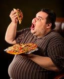 Vette mens die de pizza van de snel voedselplak eten Ontbijt voor te zware persoon Stock Afbeelding