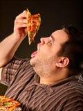 Vette mens die de pizza van de snel voedselplak eten Ontbijt voor te zware persoon Stock Foto