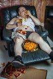 Vette mens die en het letten op televisie eten stock afbeelding