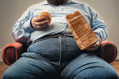 Vette mens die hamburger eet royalty-vrije stock afbeelding