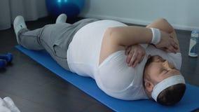 Vette mens die nauwelijks zitten-UPS op mat doen thuis, zwaarlijvigheidsmoeilijkheden, zwakke spieren stock video