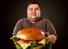 Vette mens die snel voedsel eten hamberger Ontbijt voor te zware persoon Royalty-vrije Stock Foto's