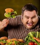 Vette mens die snel voedsel eten hamberger Ontbijt voor te zware persoon Royalty-vrije Stock Afbeeldingen