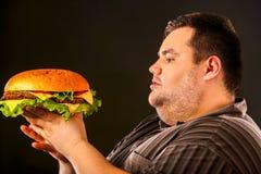 Vette mens die snel voedsel eten hamberger Ontbijt voor te zware persoon Stock Fotografie