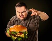 Vette mens die snel voedsel eten hamberger Ontbijt voor te zware persoon Stock Afbeeldingen