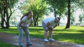 Vette paarjogging in park, steun elkaar, wederzijdse wens om gewicht te verliezen stock footage