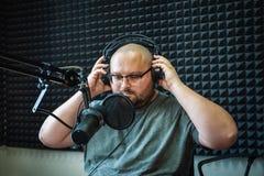 Vette radiopresentator of gastheer in radiostationstudio met hoofdtelefoons en microfoon, portret van de werkende mens royalty-vrije stock afbeeldingen