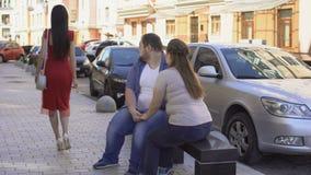 Vette vrouw boos bij vriend die mooie dame bekijken die door straat, conflict overgaan stock video