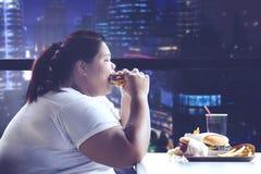 Vette vrouw die diner in het restaurant hebben royalty-vrije stock afbeeldingen