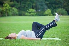 Vette vrouw die door oefeningsbeen naar omhoog liggen stock afbeeldingen