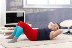 Vette vrouw die gymnastiek thuis doet stock afbeeldingen