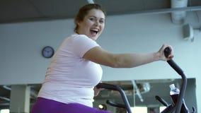 Vette vrouw die intens op stationaire fiets uitoefenen stock videobeelden