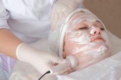 Vette vrouw in het de kosmetiekcentrum De schoonheidsspecialist in handschoenen houdt de elektrode van de massageapparaten en maa stock foto's