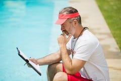 Vettura di nuotata che esamina lavagna per appunti vicino al poolside Immagine Stock