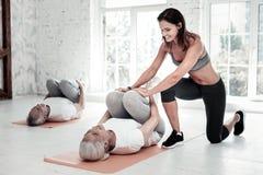 Vettura entusiasta che aiuta donna pensionata durante l'allenamento Fotografia Stock