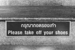 Veuillez enlever votre signe de chaussures Photo stock