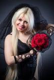 Veuve noire dans la peine avec des fleurs avec un voile Photographie stock libre de droits