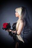 Veuve noire dans la peine avec des fleurs avec un voile Images libres de droits