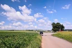 Veverske Kninice,捷克共和国- 2018年6月02日:与道路的春天moravian风景与黑汽车欧宝的花田之间 免版税图库摄影