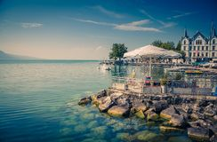 Vevey-Marche on stone shore of Lake Leman Geneva in Vevey, Switz. View of Vevey-Marche and outdoor cafe umbrellas and tables on the stone shore of the Lake Leman royalty free stock photography