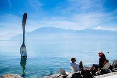 Vevey, Zwitserland - de kust van Meergenève met de Vork van moderne de installatiekunst van Vevey met de Zwitserse mening van alp stock foto's