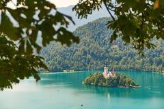 Vew del lago Bled con le montagne, isola e chiesa di pellegrinaggio, vista dall'iarda superiore sanguinata del castello, Slovenia Fotografia Stock