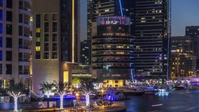 View of Dubai Marina Towers and canal in Dubai day to night timelapse. Vew of Dubai Marina embankment with Towers, restaurants on pier and yachts from bridge in stock footage