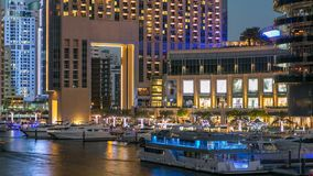 View of Dubai Marina Towers and canal in Dubai day to night timelapse. Vew of Dubai Marina embankment with yachts and modern Towers near mall from bridge in stock video footage