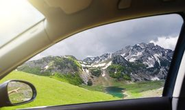 Mountain lake and meadow from a car window stock image