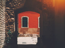 Vew through old archway to window on red wall. Single old arc window on red wall of facade of residential house in Barcelona Born district on sunny day, view Royalty Free Stock Image