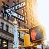 Väg för New York City vägmärke ett med fot- ljus för trafik på gatan under solnedgångljus Arkivfoto