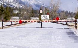 Väg stängt tecken och port som blockerar vägtillträde under vintern tim Royaltyfri Fotografi