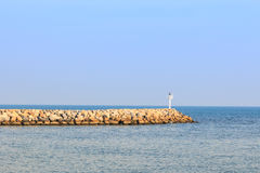 Vågbrytare i havet med fyrljus på det Royaltyfri Foto