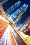 Vägen gräver ljusa slingor på moderna stadsbyggnadsbakgrunder I Royaltyfri Foto