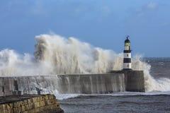 Vågor som kraschar över den Seaham fyren Arkivfoton