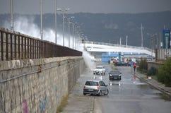Vågor som översvämmar vågbrytaren och bilar Arkivbilder
