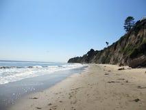 Vågor sveper på stranden bredvid den högväxta klippan Arkivbilder