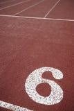 Vägvisare för nummer sex i ett idrotts- rinnande spår Arkivfoton