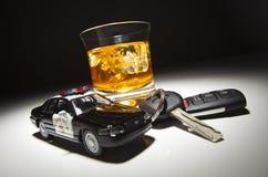 Véhicule de police à côté de boisson alcoolisée et de clés Images libres de droits