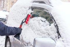 Véhicule sur une route de l'hiver La main de l'homme nettoie la fenêtre de voiture de la neige Photographie stock libre de droits