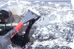 Véhicule sur une route de l'hiver La main de l'homme érafle la glace et la neige Photographie stock