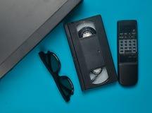 Vhs球员,录象带, 3d,在蓝色背景的电视遥控 过时媒介技术 顶视图 免版税库存照片