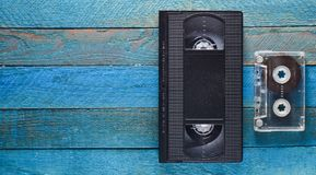VHS, ακουστική κασέτα σε έναν μπλε ξύλινο πίνακα Αναδρομική τεχνολογία μέσων από τη δεκαετία του '80 διάστημα αντιγράφων Τοπ όψη Στοκ Φωτογραφίες