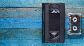 VHS, Audiokassette auf einem blauen Holztisch Retro- Medientechnik von den achtziger Jahren Kopieren Sie Platz Beschneidungspfad  Stockfotos