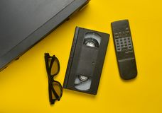 Vhs player, video cassette, 3d glasses on a yellow background. Obsolete media technologies. Top view. Vhs player, video cassette, 3d glasses, tv remote on a Royalty Free Stock Photos