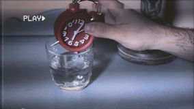 Alarm clock in water detail VHS. VHS screen capture: the hand of a tired man in bed putting a ringing alarm clock into a glass of water to make it stop royalty free stock photos