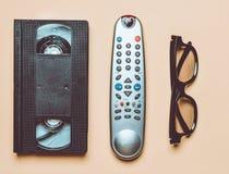 Vhs, telecontrol de la TV, vidrios 3d en un fondo de papel amarillo Entretenimiento 90s Visión superior Endecha plana foto de archivo libre de regalías