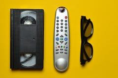 VHS, telecontrole da tevê, vidros 3d em um fundo de papel amarelo Entretenimento 90s Vista superior Foto de Stock Royalty Free