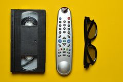 Vhs, TV remote, 3d glasses on a yellow paper background. Entertainment 90s. Top view. Flat lay Royalty Free Stock Photo