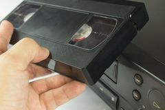 VHS videocassette in hand next to VCR. Before including movie, close-up royalty free stock images